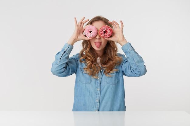 Молодая красивая женщина с длинными светлыми волнистыми волосами держит в руках пончики, просматривает пончики и показывает язык, изолированный на белом фоне.