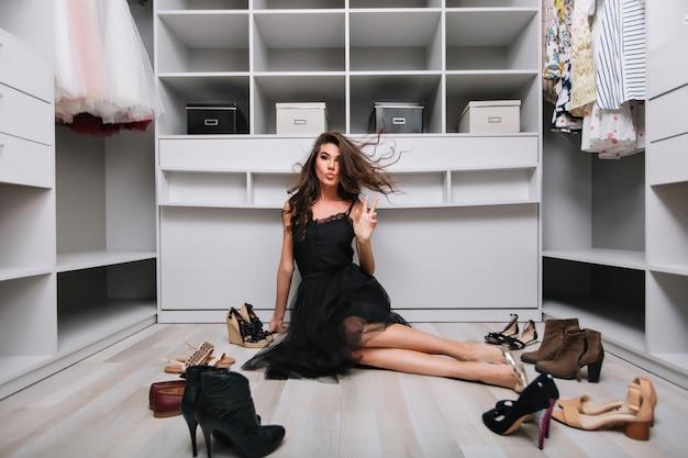 Giovane bella donna con lunghi capelli ricci che volano in aria seduto sul pavimento in un bel guardaroba, spogliatoio. molte scarpe intorno a lei, che mostrano pace. indossa un abito nero elegante e scarpe d'argento.