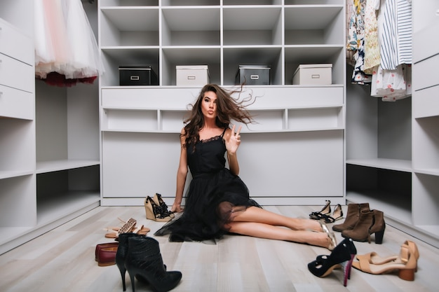 素敵なワードローブ、楽屋の床に座って空気を飛んでいる長い巻き毛を持つ若いきれいな女性。彼女の周りにはたくさんの靴があり、平和を示しています。エレガントな黒のドレスと銀の靴を履いています。