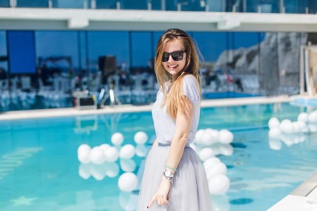 Молодая красивая женщина с длинными волосами и в черных очках стоит возле бассейна