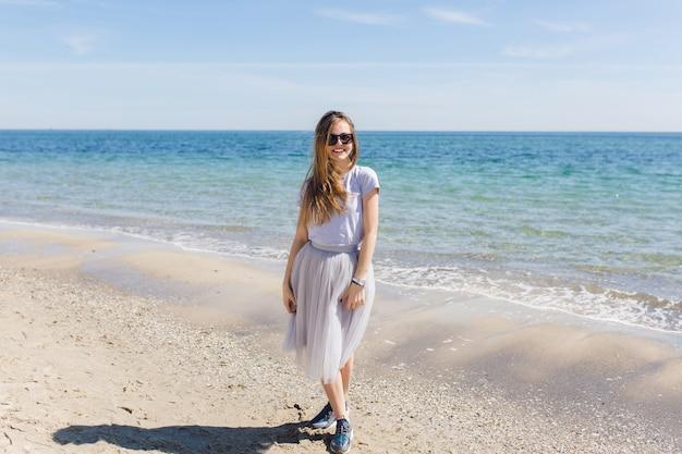 長い髪の若いきれいな女性は青い海の近くに滞在します。