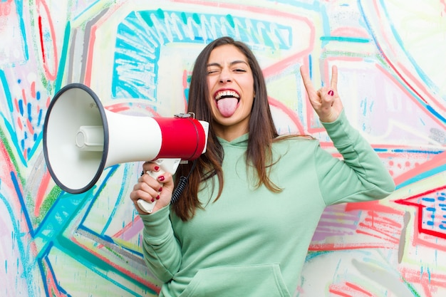 Young pretty woman with a megaphone against graffiti wall