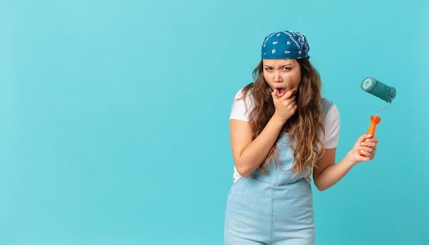 입과 눈을 크게 뜨고 턱에 손을 대고 벽에 그림을 그리는 젊은 예쁜 여자