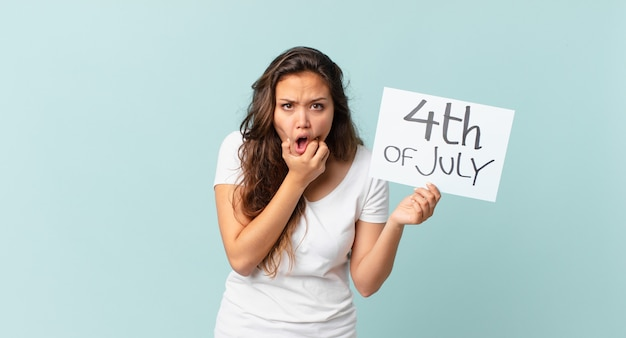Молодая красивая женщина с широко открытыми глазами и ртом, положив руку на концепцию дня независимости подбородка