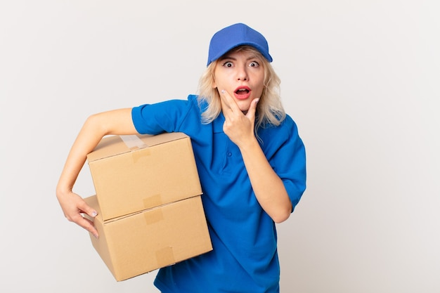 Young pretty woman with mouth and eyes wide open and hand on chin. package delivering concept