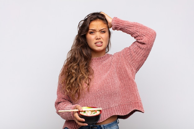 Young pretty woman with noodles feeling stressed, worried, anxious or scared, with hands on head, panicking at mistake