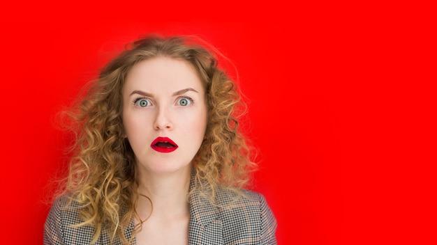 Молодая красивая женщина с открытым ртом потрясена красной стеной, веб-баннер