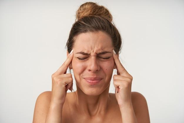 Giovane donna graziosa con la faccia dolorante, posa su bianco con le dita indice sulle tempie, chiudendo gli occhi a causa del mal di testa