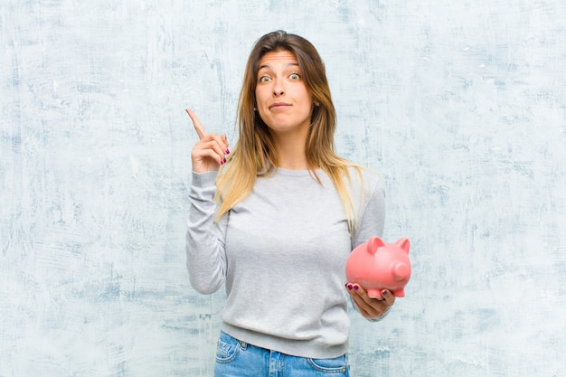 Young pretty woman with a piggy bank against grunge wall
