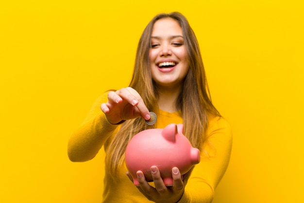 Young pretty woman with a piggy bank