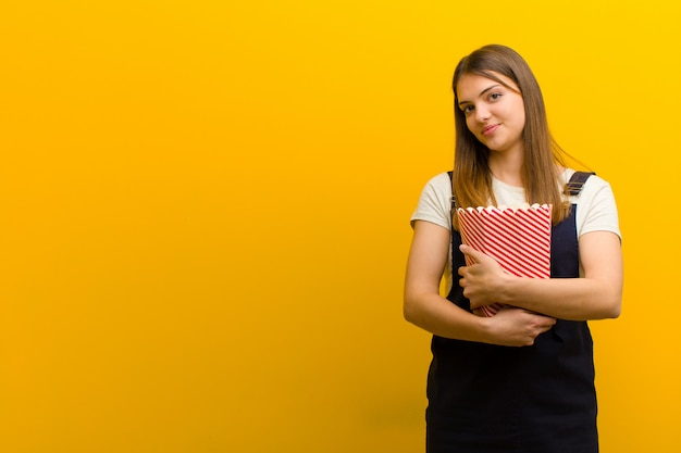 Young pretty woman with  pop corns  against orange