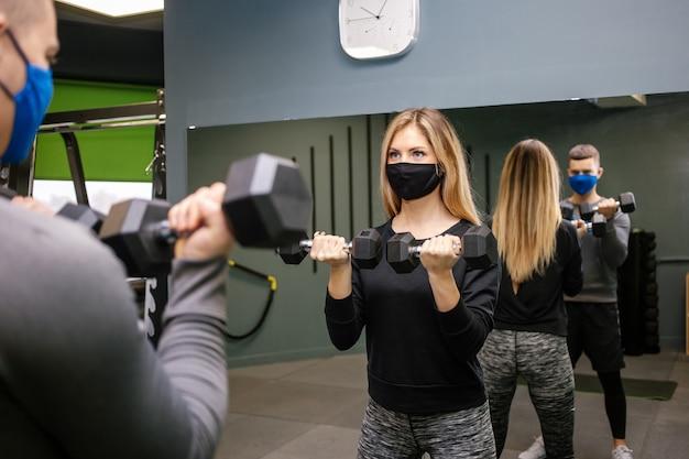 Covid-19 전염병 동안 체육관에서 개인 트레이너와 함께 운동하는 보호 마스크를 가진 젊은 예쁜 여자. 얼굴 보호 마스크에 스포츠 사람.