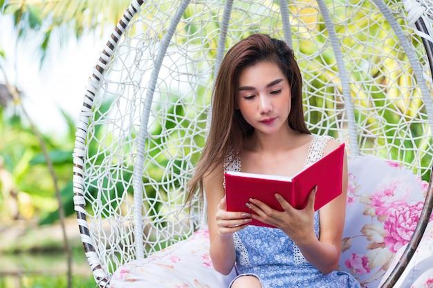 Молодая милая женщина с красным дневником в парке