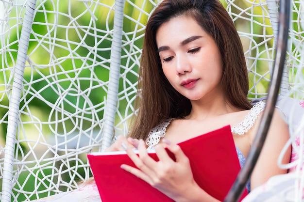 Giovane donna graziosa con il diario rosso nel parco