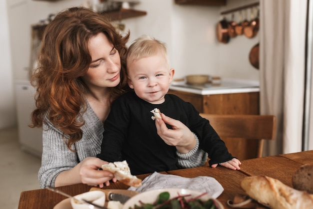 Young pretty woman with red hair in knitted sweater feeding her little smiling son that joyfully