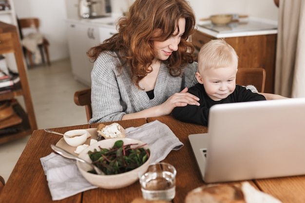Young pretty woman with red hair in knitted sweater and little son sitting at the table with food and dreamily watching cartoons on laptop