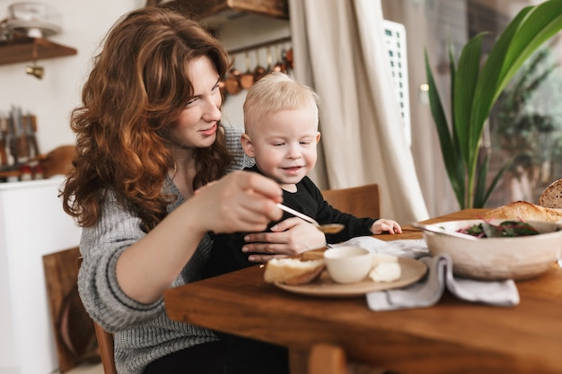 Young pretty woman with red hair in knitted sweater sitting at the table with food happily feeding her little smiling son