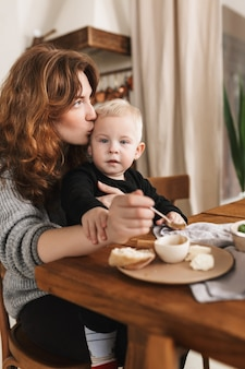 Young pretty woman with red hair in knitted sweater sitting at the table with food kissing in head her little son that dreamily