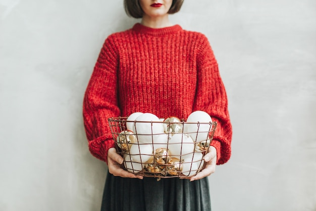 빨간 니트 스웨터와 회색 치마 크리스마스 금색과 흰색 공의 그녀의 손에 큰 바구니를 들고 젊은 예쁜 여자