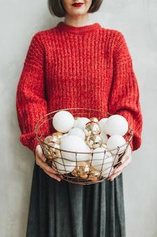 빨간 니트 스웨터와 회색 치마 크리스마스 금색과 흰색 장난감의 그녀의 손에 큰 바구니에 들고 젊은 예쁜 여자