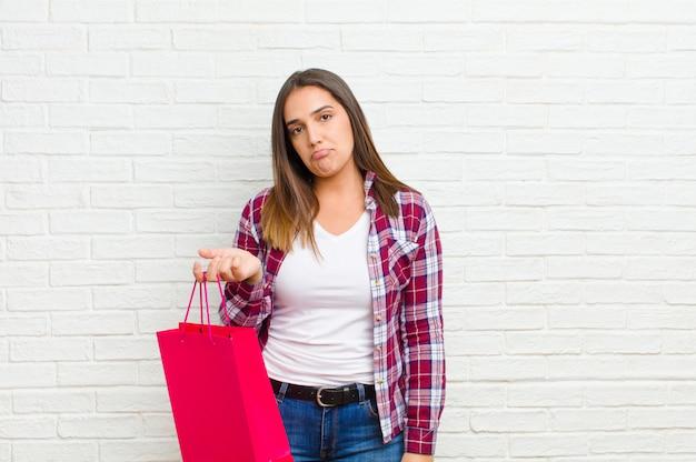 レンガの壁の質感に対して買い物袋を持つ若いきれいな女性