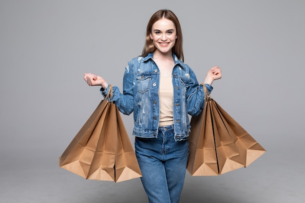 Young pretty woman with shopping packages on gray wall