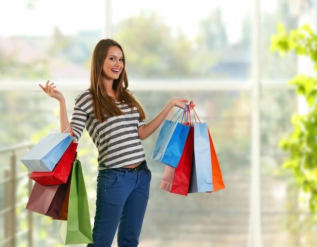 店内のショッピングパッケージを持つ若いきれいな女性