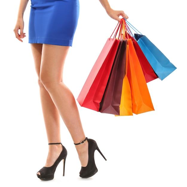 白のショッピングパッケージを持つ若いきれいな女性