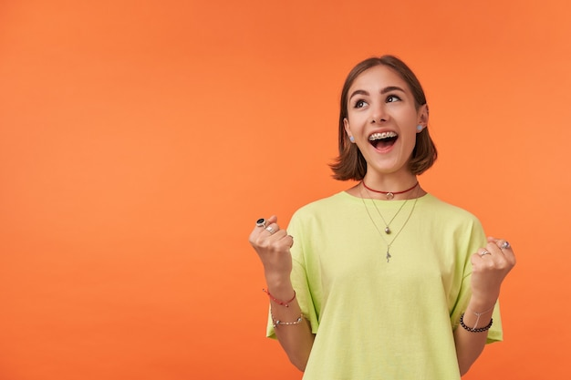 Young pretty woman with short brunette hair smiling. very excited girl look to left upper corner at the copy space over orange wall. wearing green t-shirt, necklace, bracelets and rings