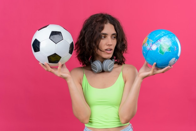 A young pretty woman with short hair in green crop top in headphones holding globe and soccer ball