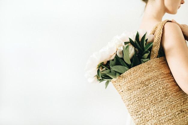 白い背景に白い牡丹の花の花束とわらのバッグを持つ若いきれいな女性。夏の美しさのコンセプト。