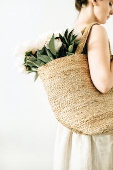 Молодая красивая женщина с соломенной сумкой с букетом белых пионов на белом