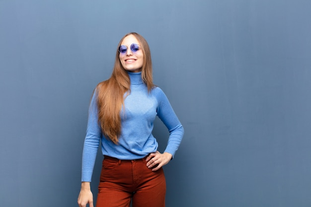 Young pretty woman with sunglasses against blue wall with a copy space