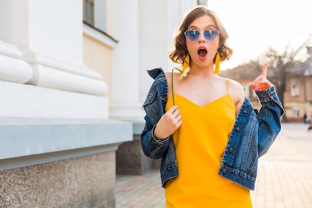 驚きの顔の表情、感情的、ショックを受けた感情、スタイリッシュなアパレル、デニムジャケット、黄色のトップ、花を持って、晴れた夏、流行の面白いサングラスを身に着けている若いきれいな女性