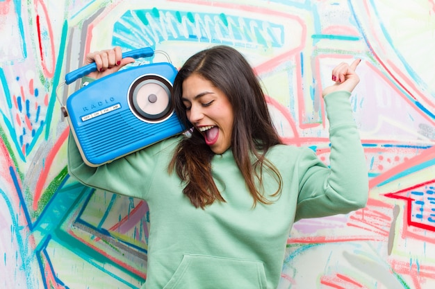 Young pretty woman with a vintage radio  graffiti wall