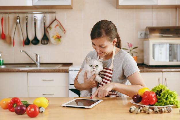 La giovane bella donna con gatto persiano bianco in cucina con tablet sul tavolo. insalata di verdure. concetto di dieta. uno stile di vita sano. cucinare a casa. prepara da mangiare.