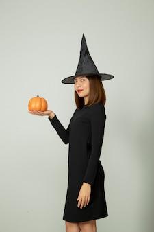 Молодая красивая женщина в шляпе ведьмы держит хэллоуин тыквенный джек o фонарь декор