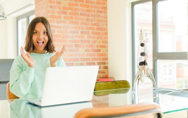 Молодая красивая женщина работает, чувствует себя счастливой, взволнованной, удивленной или шокированной, улыбается и удивляется чему-то невероятному