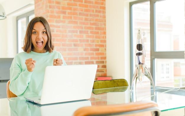 Молодая симпатичная женщина работает, чувствует себя потрясенной, взволнованной и счастливой, смеется и празднует успех, говоря