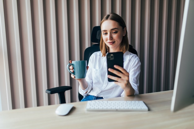 Young pretty woman working on line with a pc and phone in a desktop at office