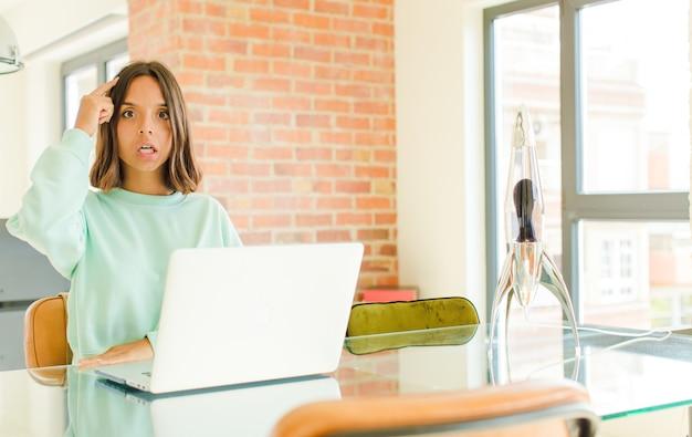 Молодая красивая женщина работает, выглядит удивленной, с открытым ртом, шокированной, осознавая новую мысль, идею или концепцию