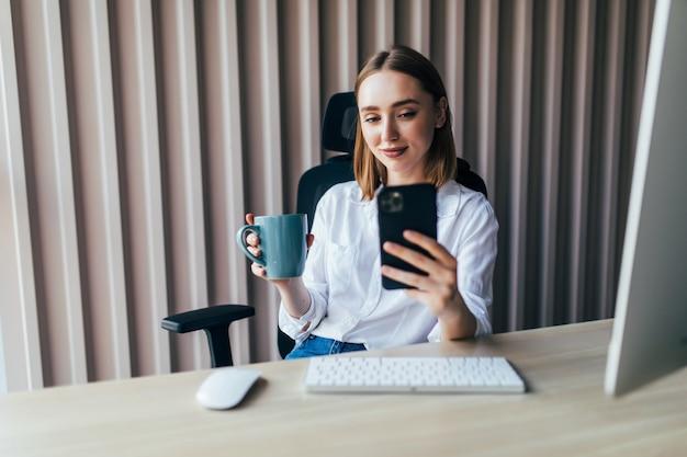 Молодая красивая женщина, работающая на линии с компьютером и телефоном на рабочем столе в офисе
