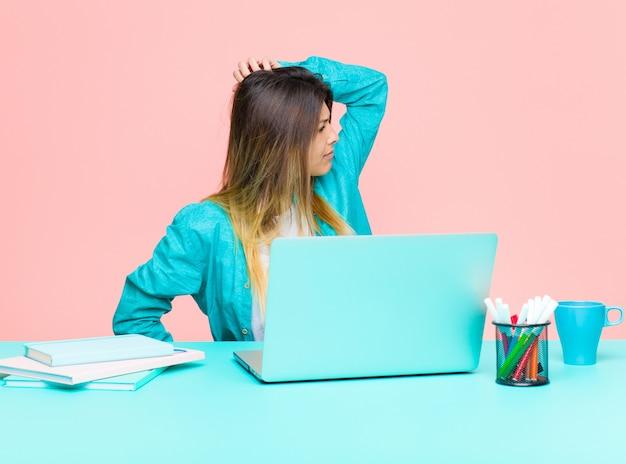 Молодая милая женщина работая с компьтер-книжкой думая или сомневаясь царапая голова чувствуя озадаченный и смущенный назад