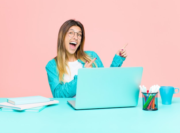 Young pretty woman working with a laptop feeling joyful and surprised, smiling with a shocked expression and pointing to the side