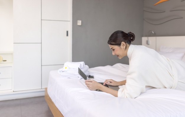 ベッドの上でラップトップで作業している若いきれいな女性