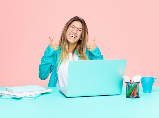 Young pretty woman working with a laptop smiling broadly looking happy, positive, confident and successful, with both thumbs up