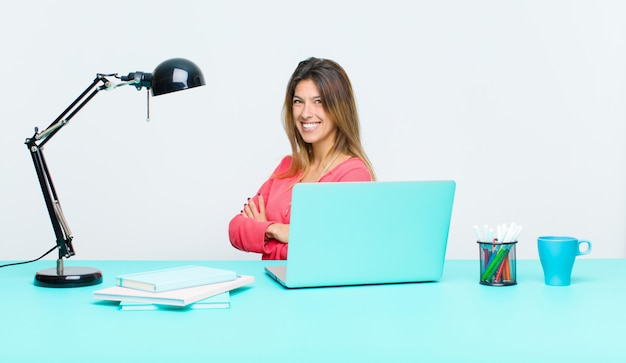 Young pretty woman working with a laptop smiling to camera with crossed arms and a happy, confident, satisfied expression, lateral view