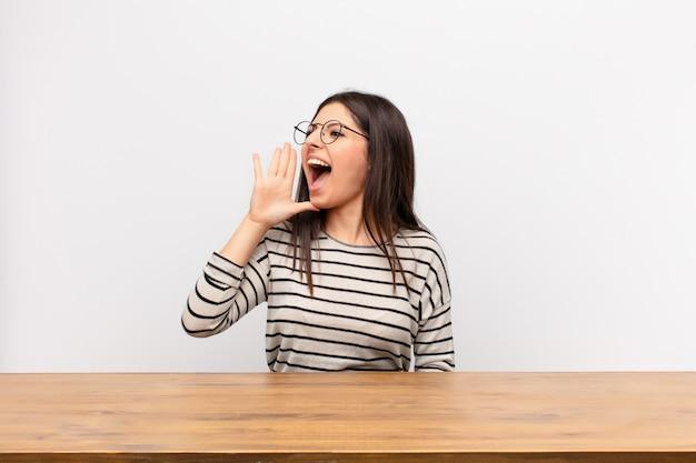 Молодая красивая женщина кричит громко и сердито, чтобы скопировать пространство на стороне, с рукой рядом с ртом, сидя за столом