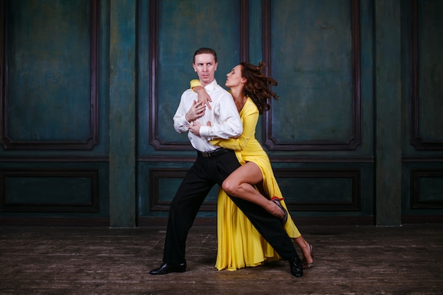 Young pretty woman in yellow dress and man dance tango