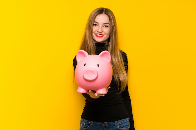 Young pretty woman over yellow wall holding a piggybank